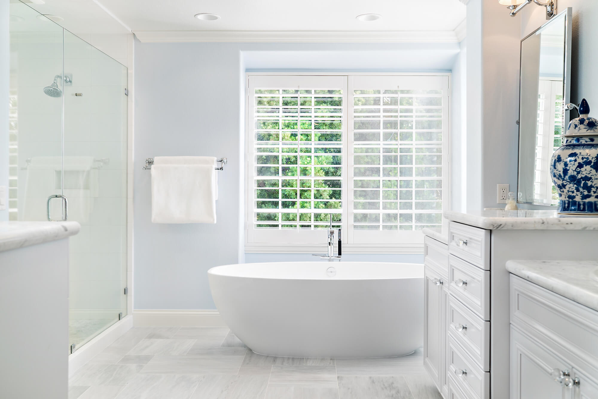 blue and white master bathroom with free standing tub and large glass shower