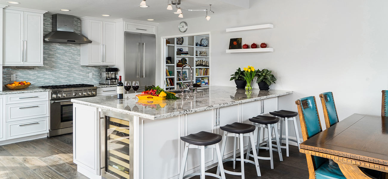 large white kitchen with dark natural wood countertops and floating shelves