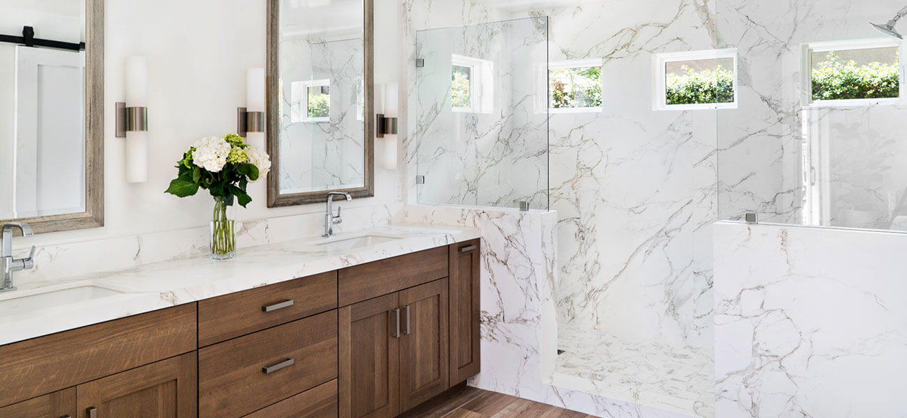 master bathroom with natural vanity cabinetry and large luxury quartz shower