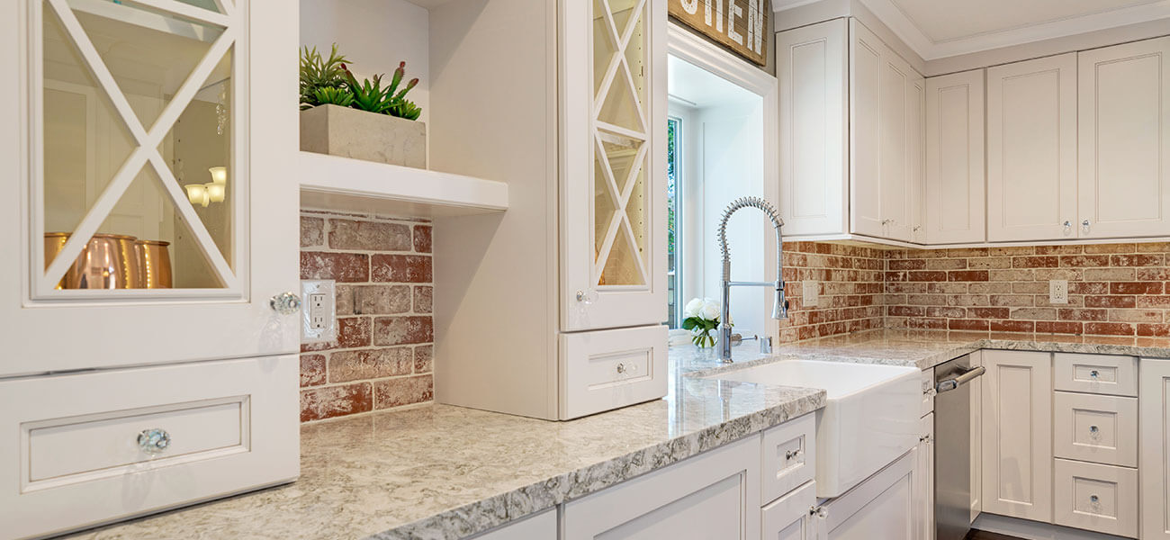 white kitchen with red brick back splash and farmhouse sink