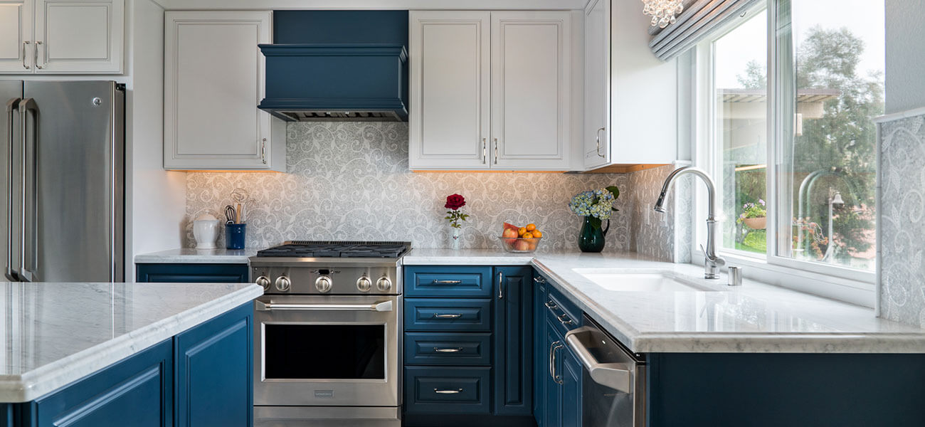 blue kitchen cabinets with marble countertops and mosaic backsplash