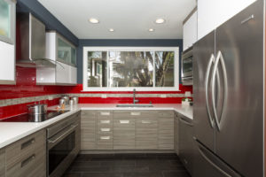 Modern Style Kitchen With Red Backsplash and Brown Cabinets