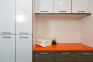 Modern Laundry Room Design With Orange Countertop