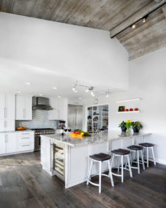 Reclaimed wood ceiling with white kitchen counter and island