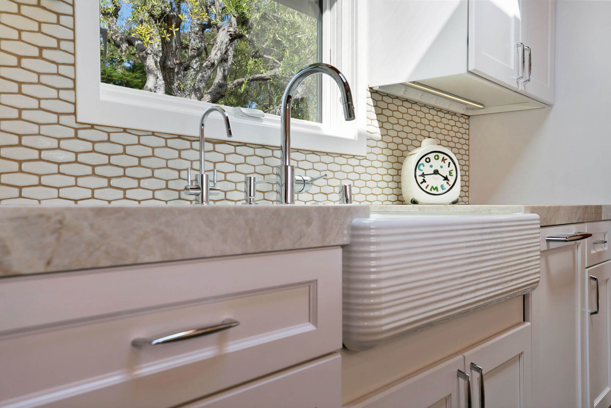 apron sink with textured detail in white kitchen