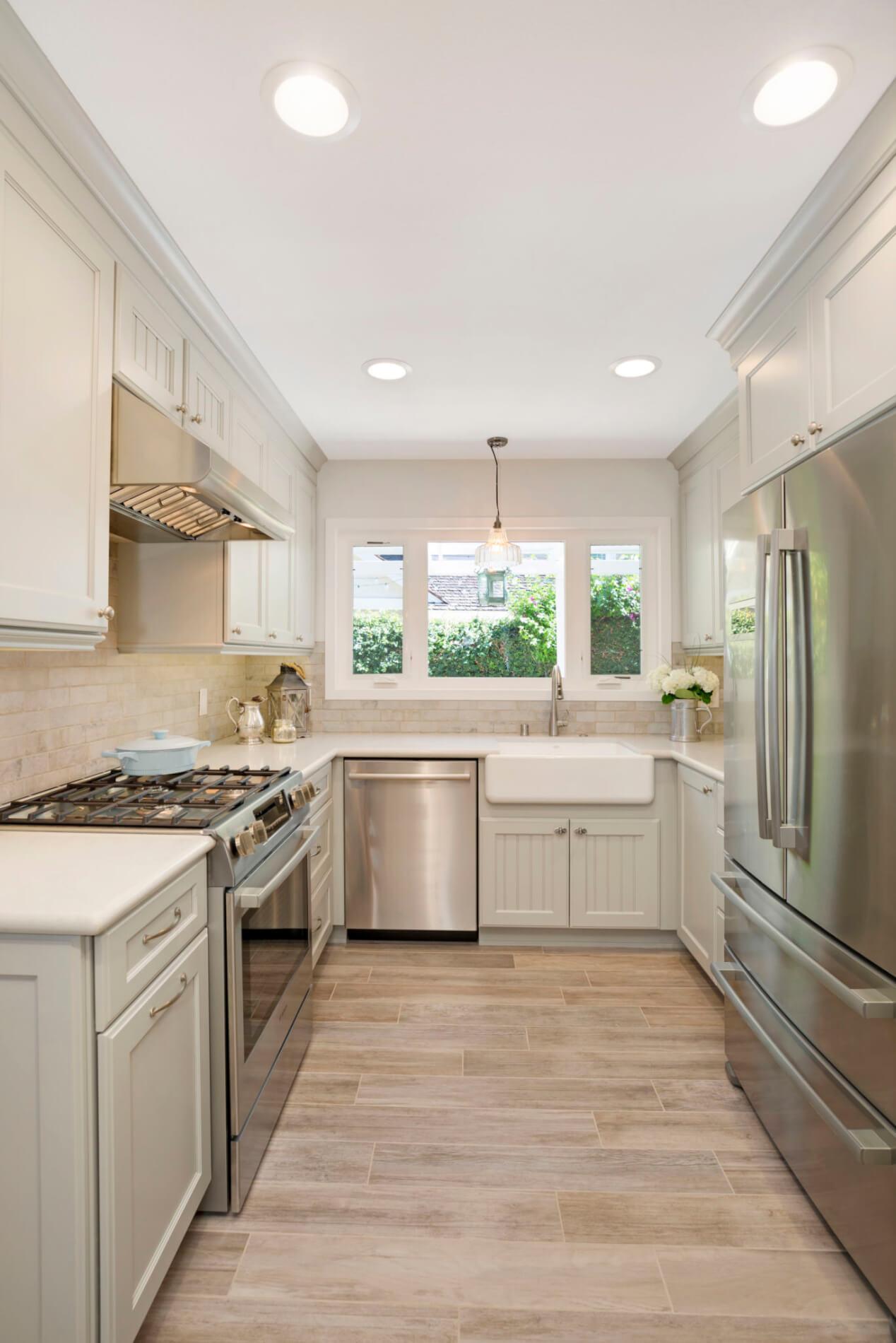 light blue kitchen cabinetry with farmhouse sink and whitewash brick backsplash