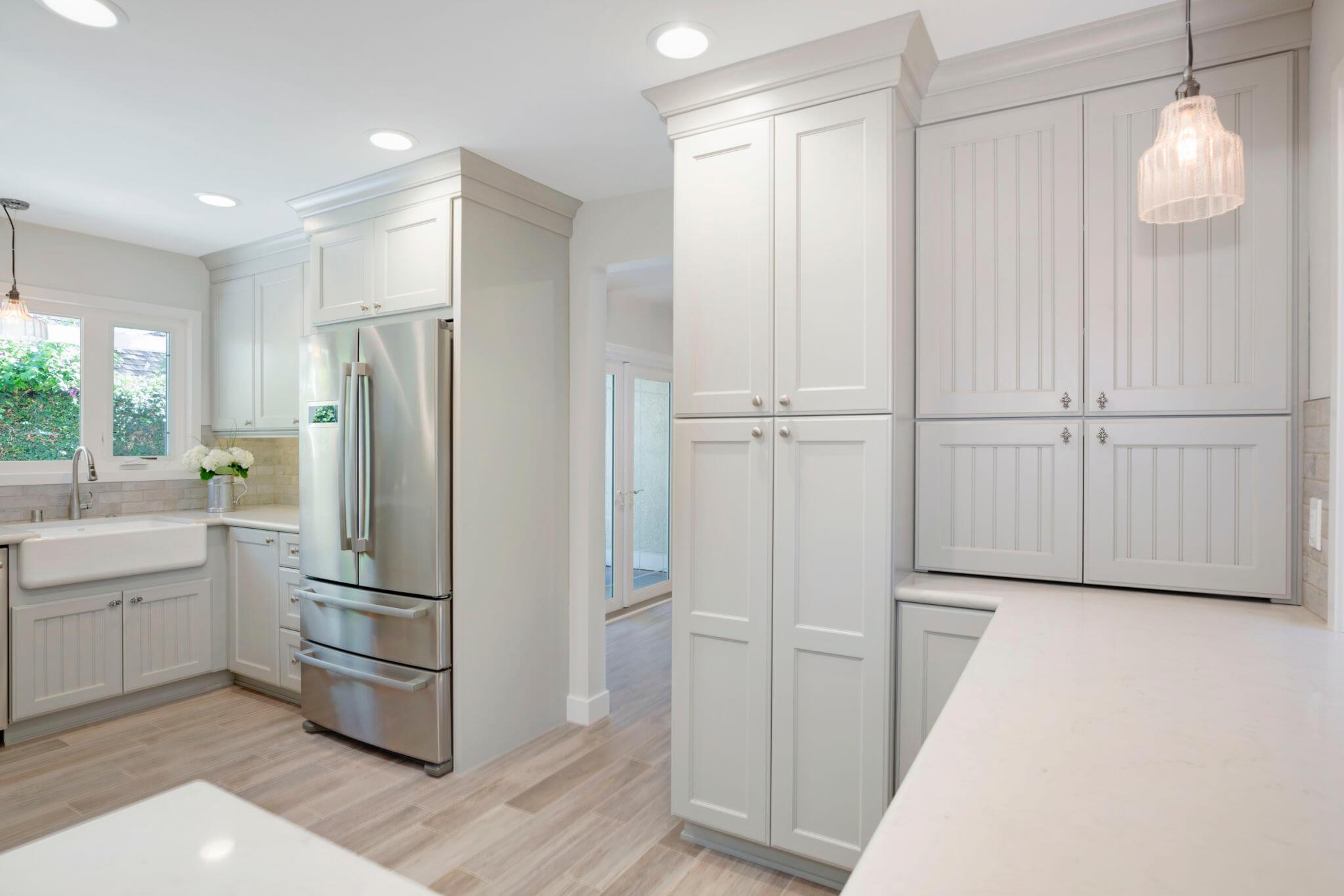 light blue custom kitchen cabinets with white countertops and stone backsplash