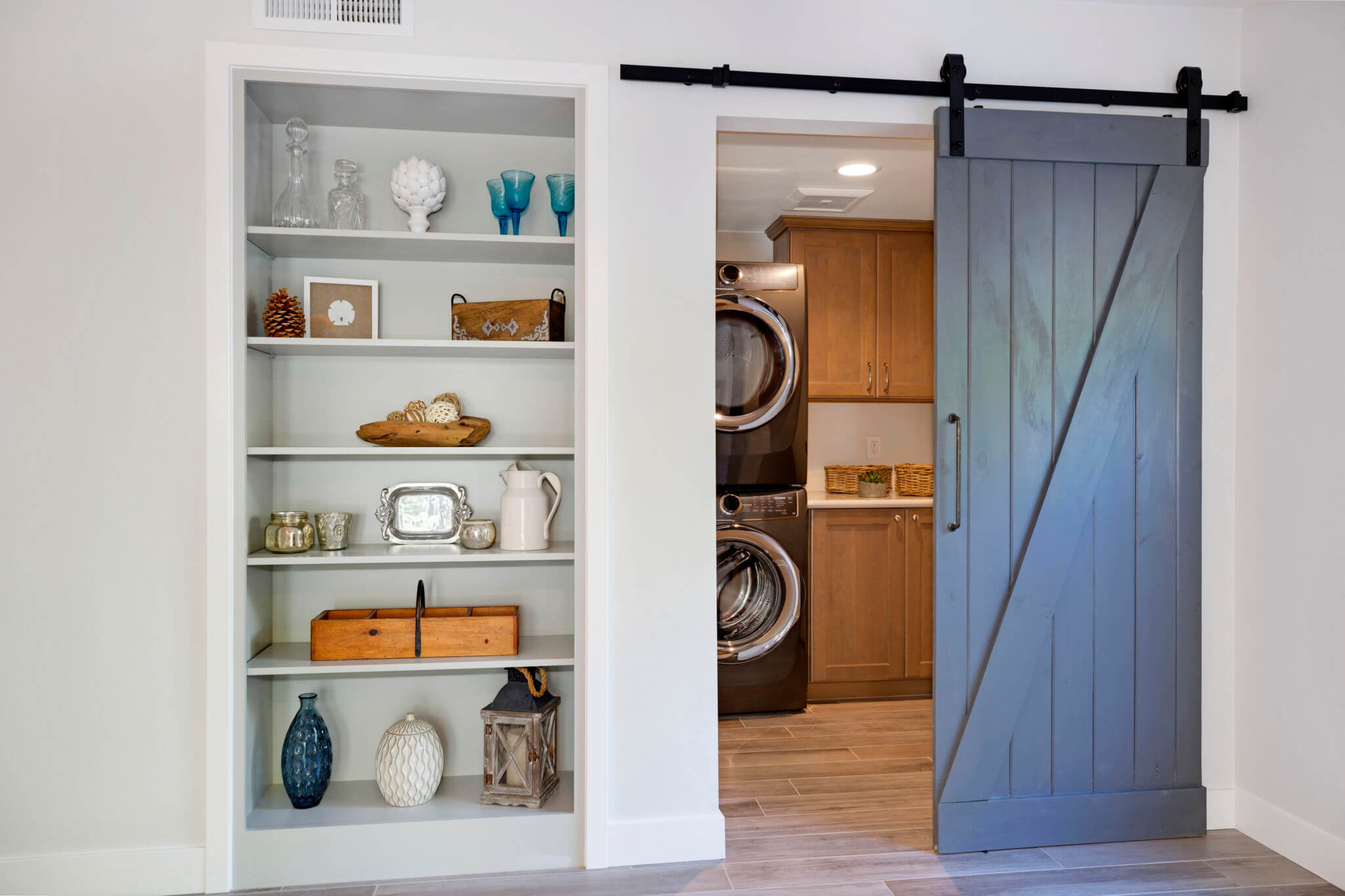laundry room with barn door and cabinet storage