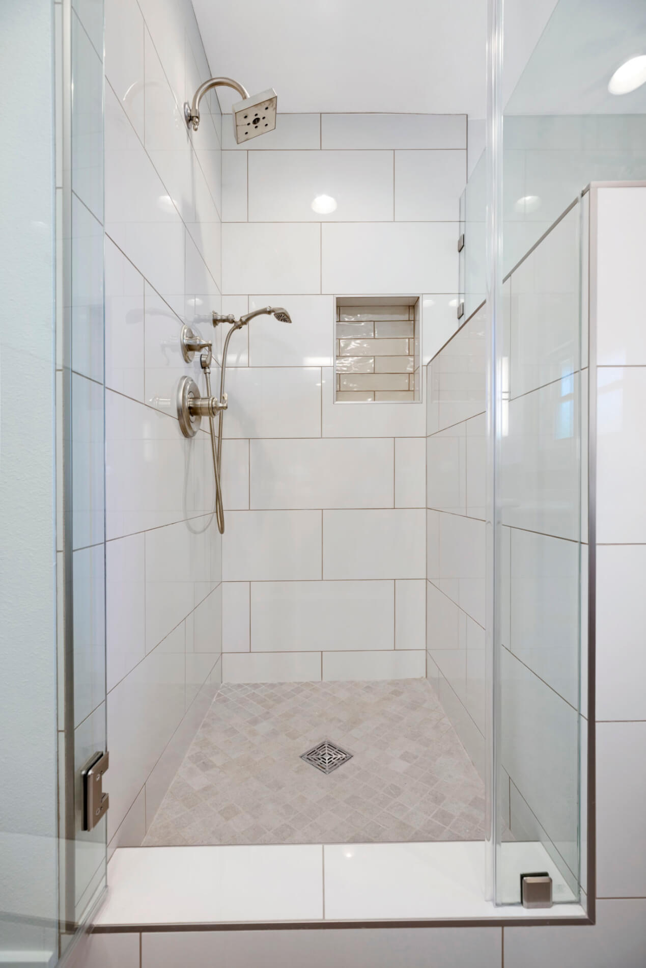 master bathroom shower with large format tile walls and mosaic flooring