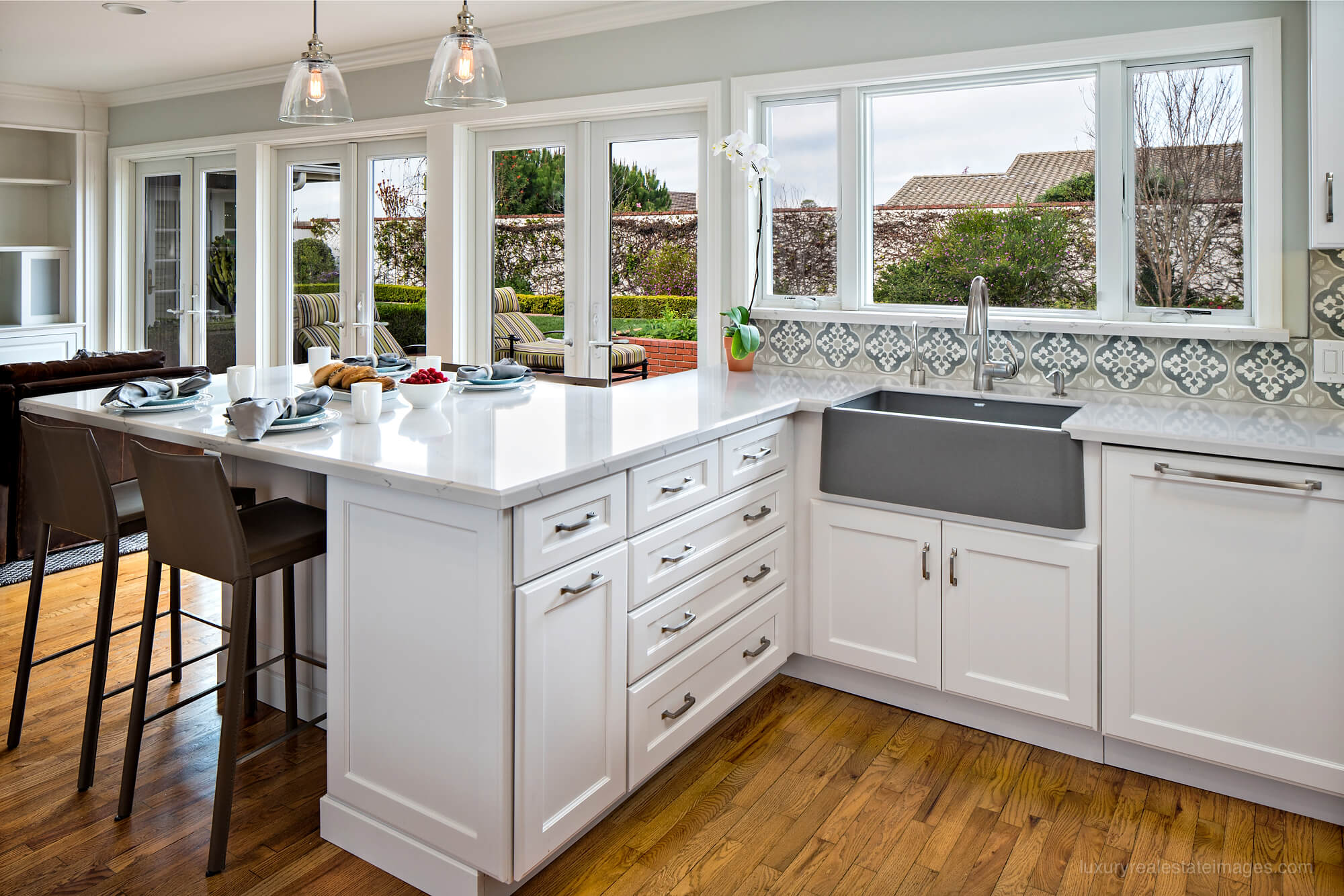 white kitchen with large peninsula and gray farmhouse sink