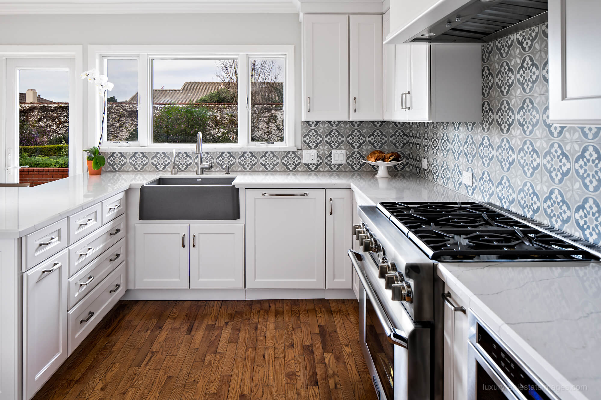 white kitchen with patterned backsplash detail and gray farmhouse sink