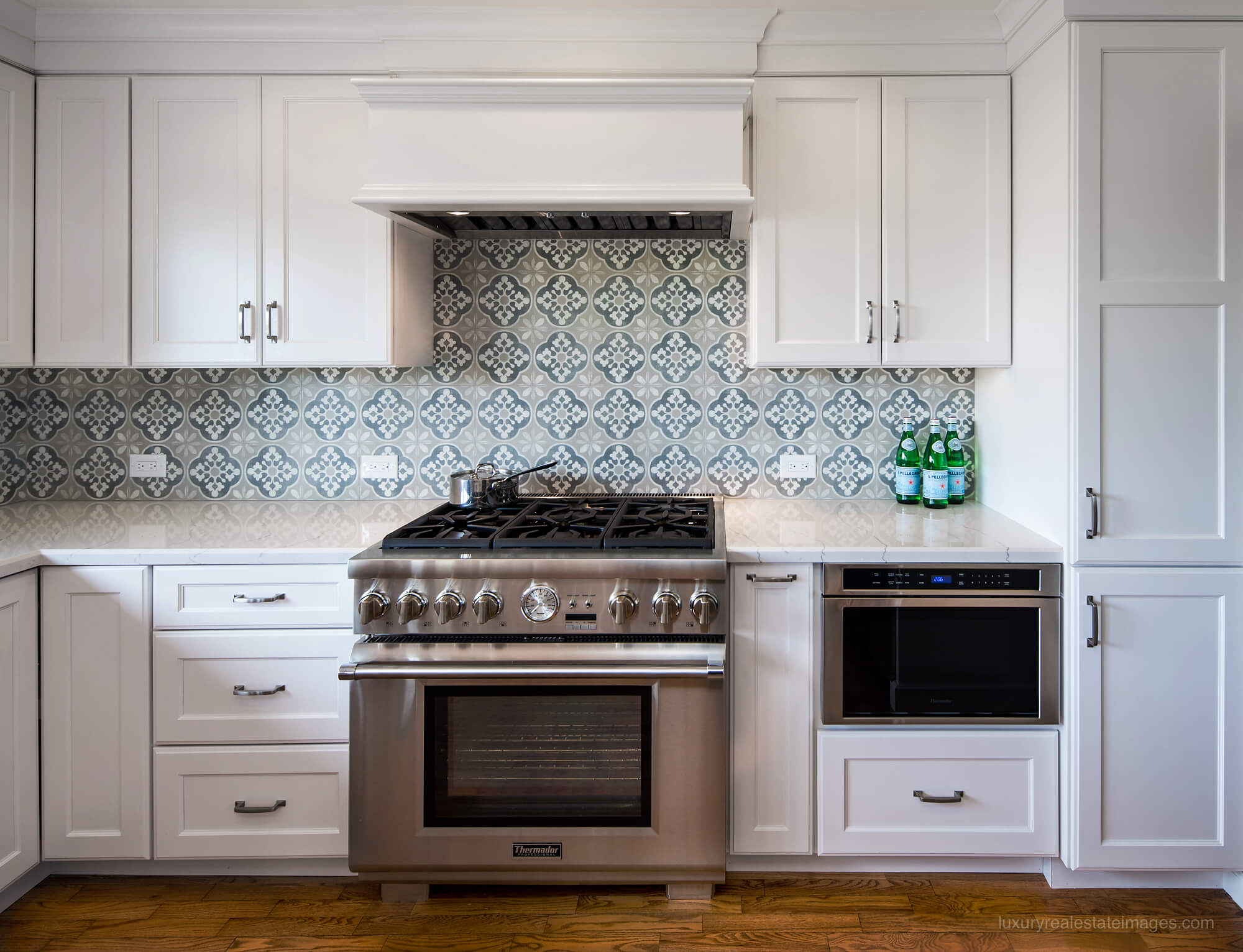 white kitchen with simple white counter top and patterned tile backsplash
