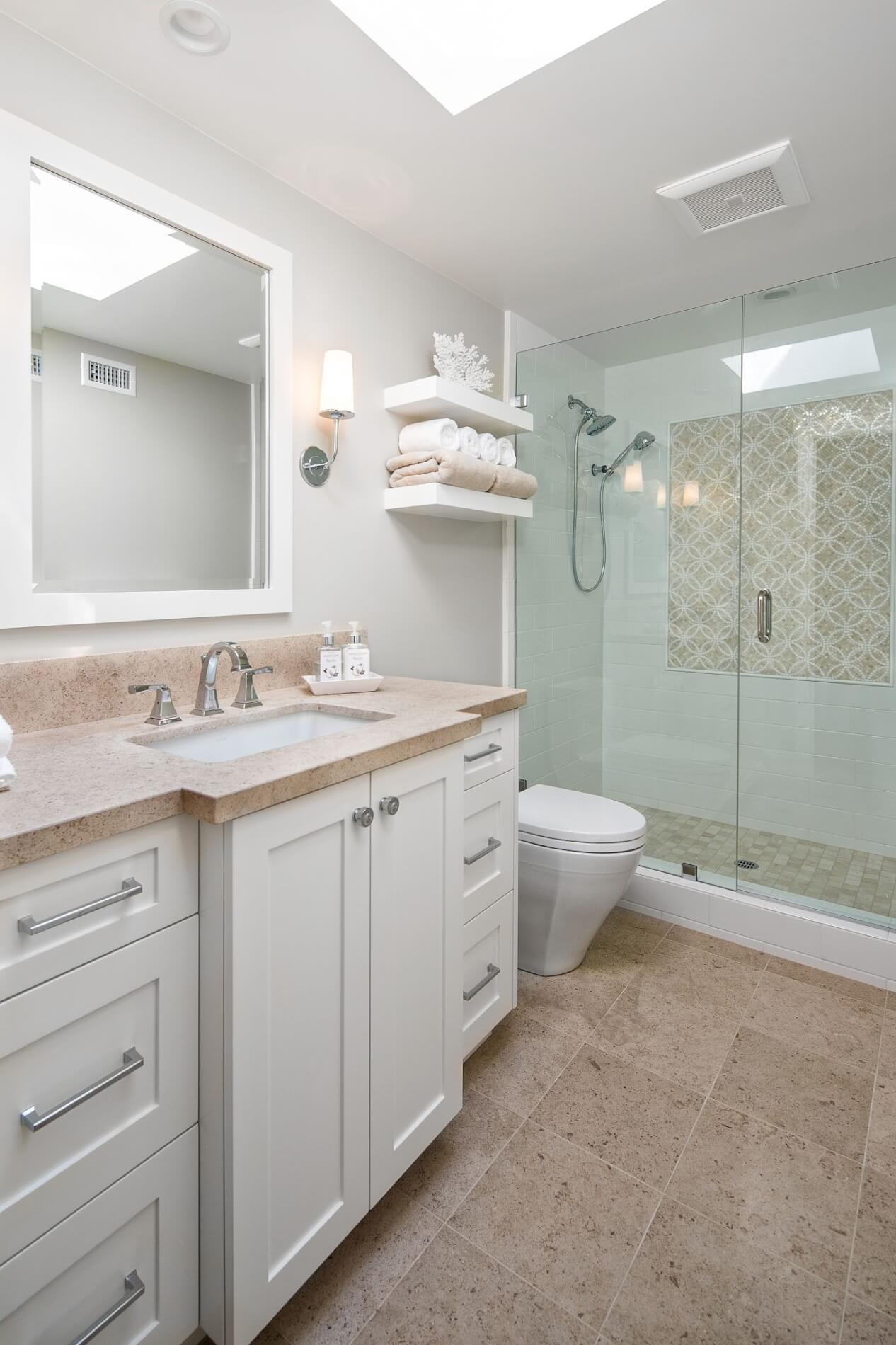 travertine in hall bathroom with white cabinets