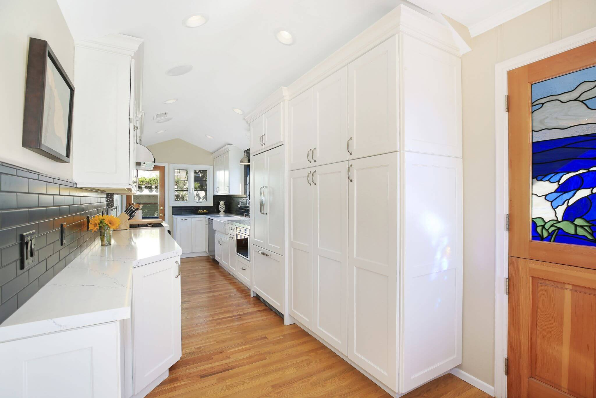 galley style kitchen with simple white cabinets and black design details
