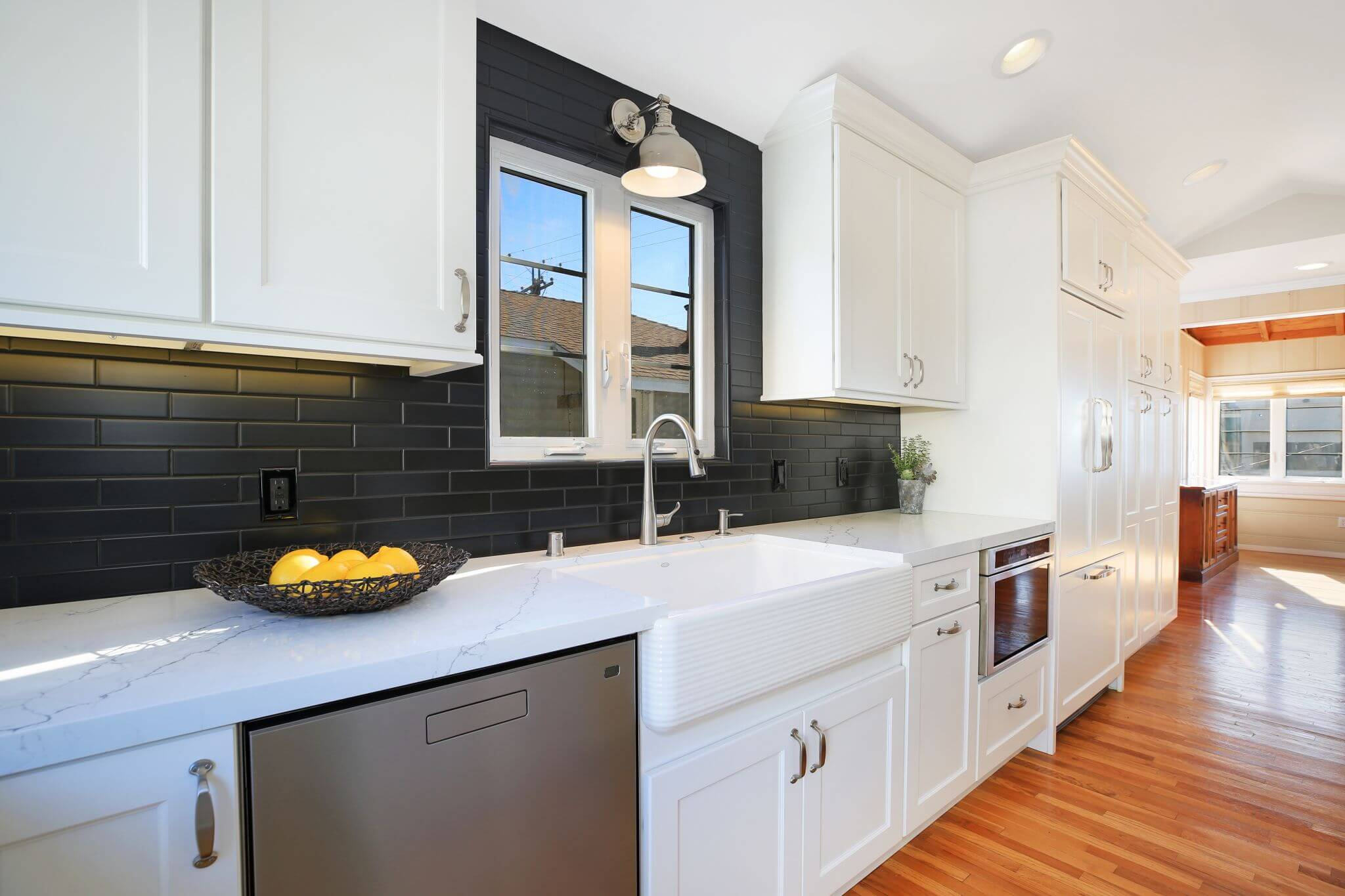 galley style kitchen with white cabinets and and black backsplash