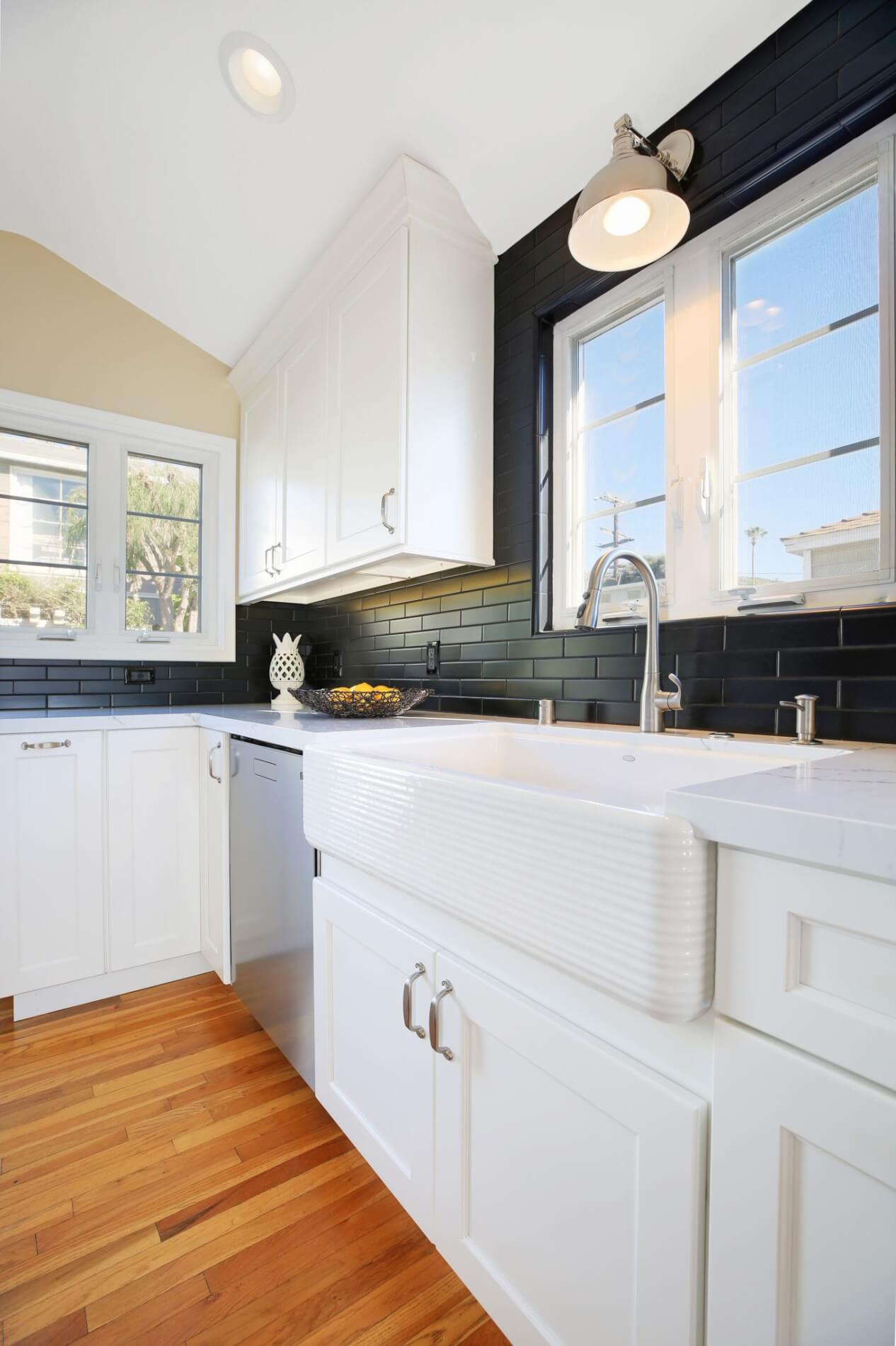 white kitchen cabinets with wood flooring and silver hardware details
