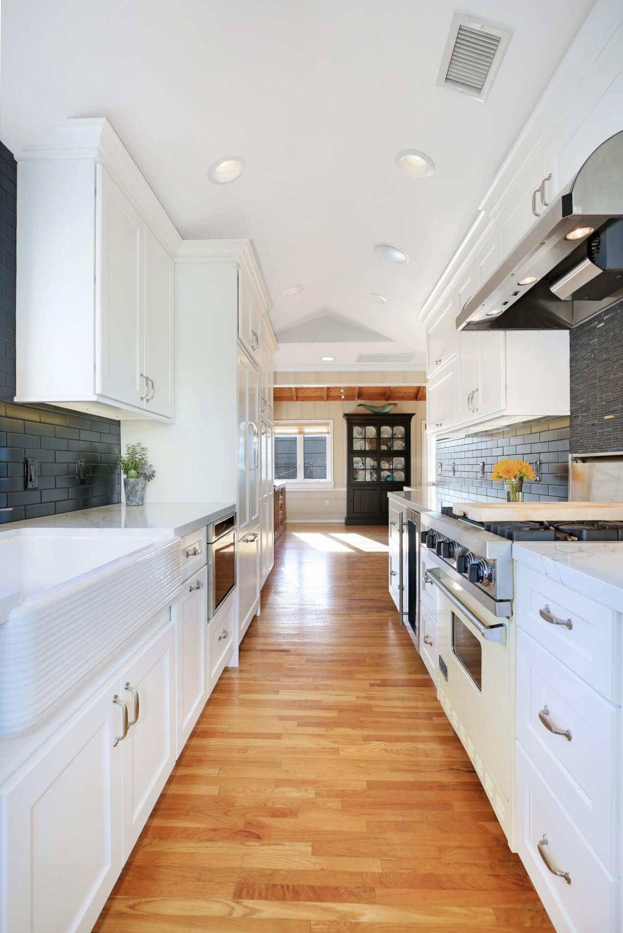 galley kitchen with white cabinets and countertops