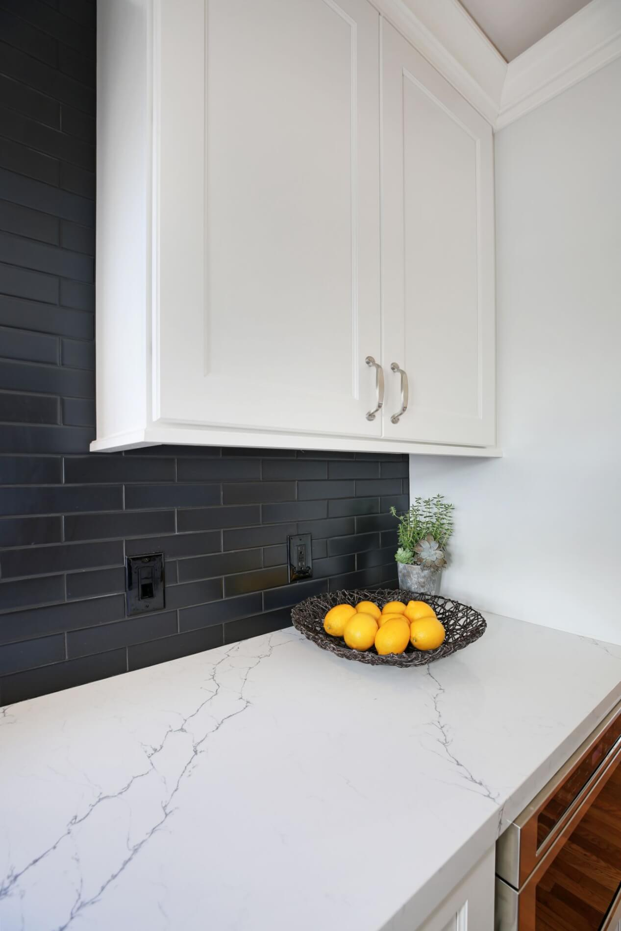 matte black tile backsplash with white kitchen cabinets and countertop