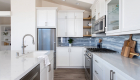 Spacious-kitchen-remodel-withlarge-white-island-andwhite-cabinetry-with-glossy-blue-backsplash