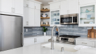 White-cabinetry-in-kitchen-remodel-with-stainless-steel-appliances-creates-bright-transitional-design