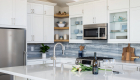 White-cabinetry-with-see-through-glass-shelving-in-kitchen-remodel