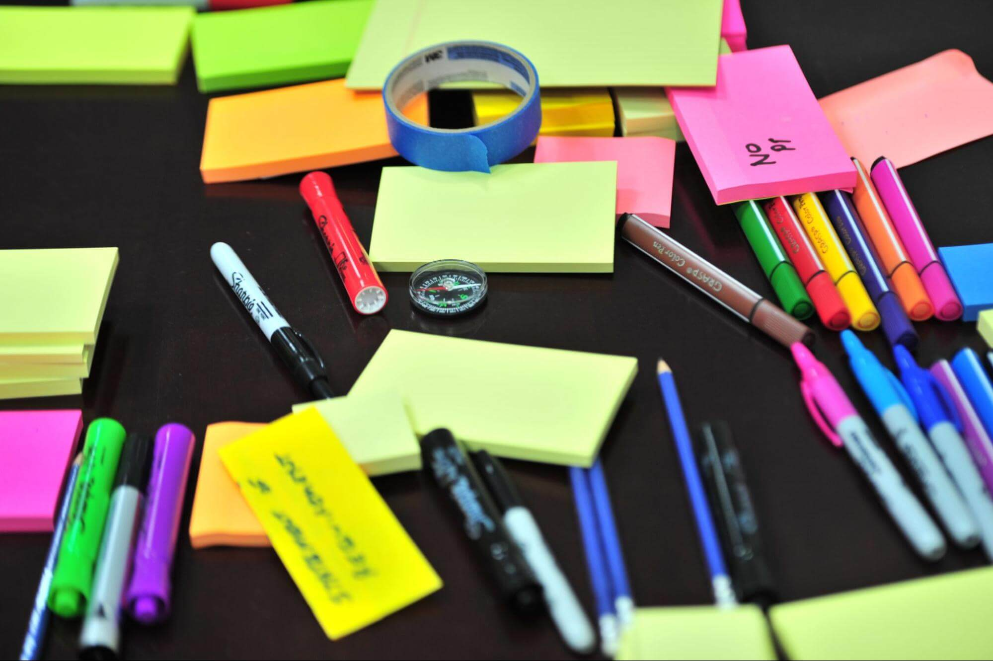 Assortment of office supplies - post-it notes, pens, highlighters, etc.