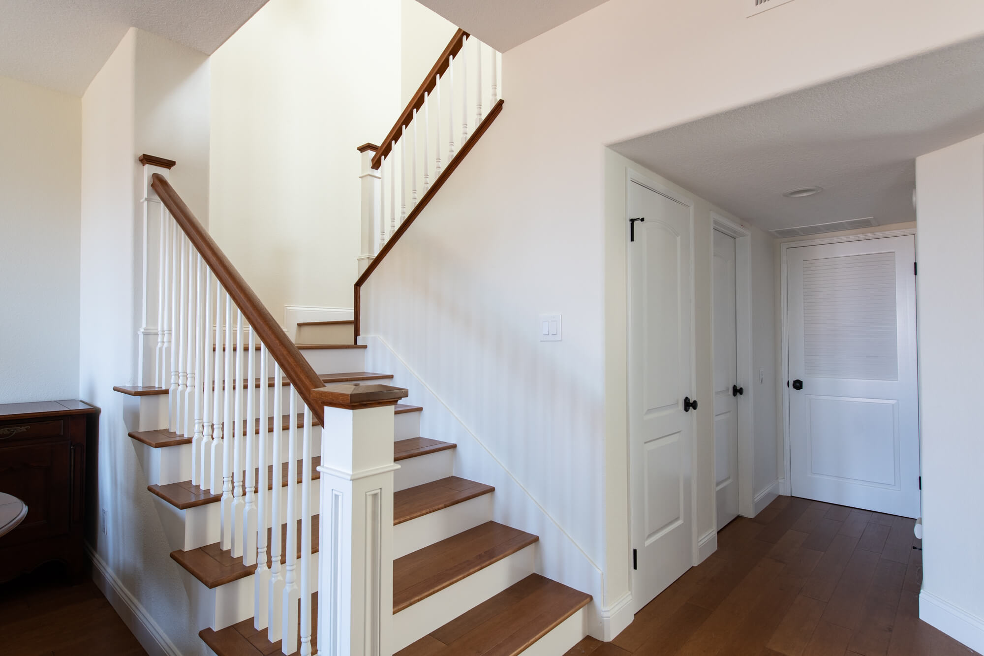 a staircase with brown treads and handrail, and a white wooden baluster