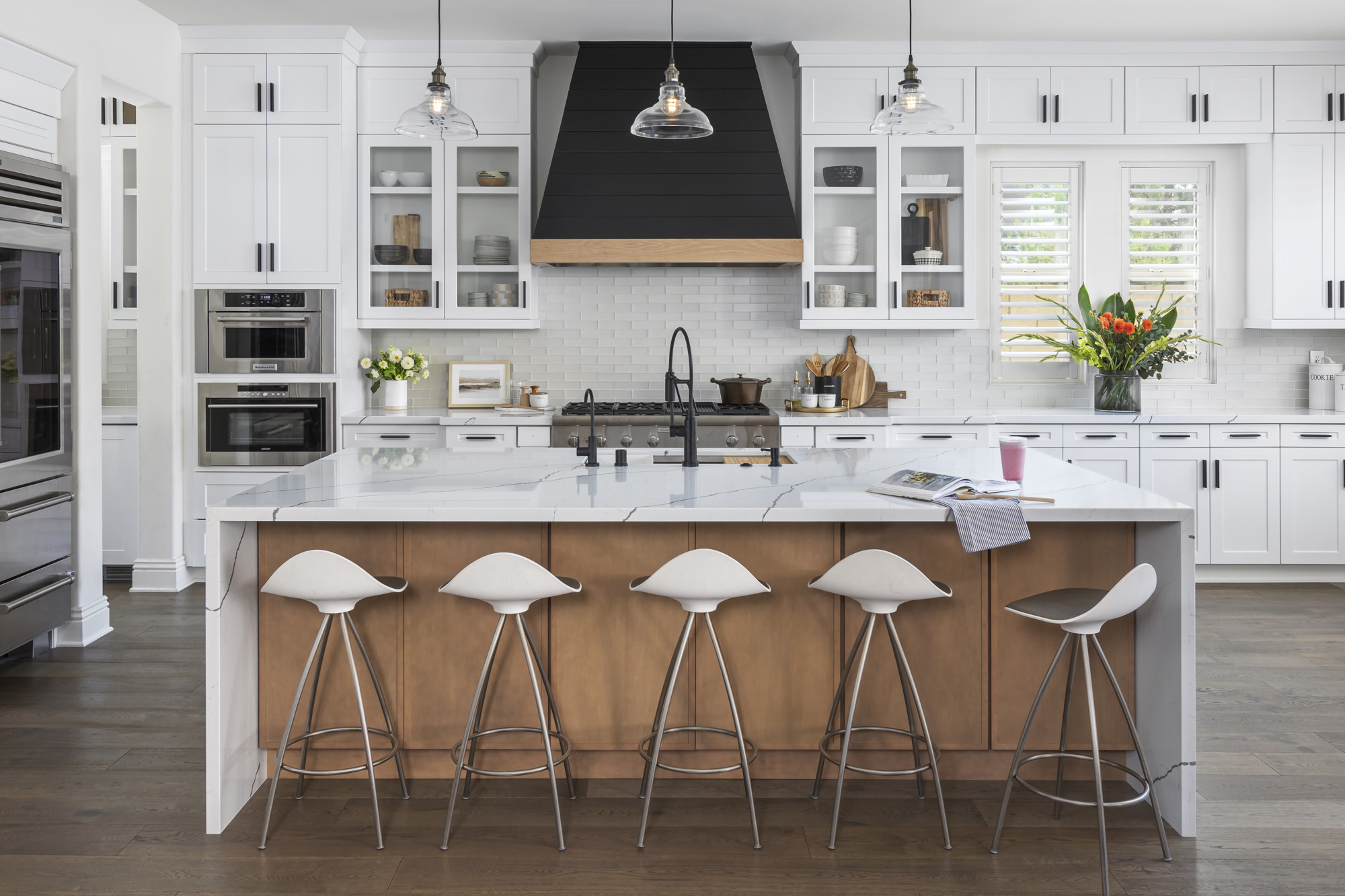 White kitchen with dominant island and wood floors and accents