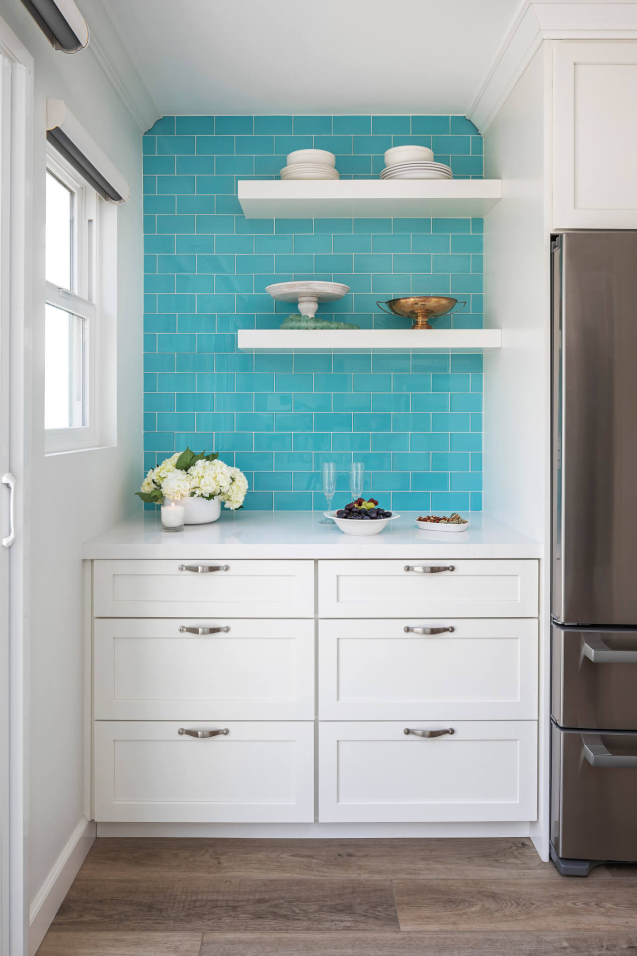 Small white butler's pantry with blue backsplash with silver hardware.