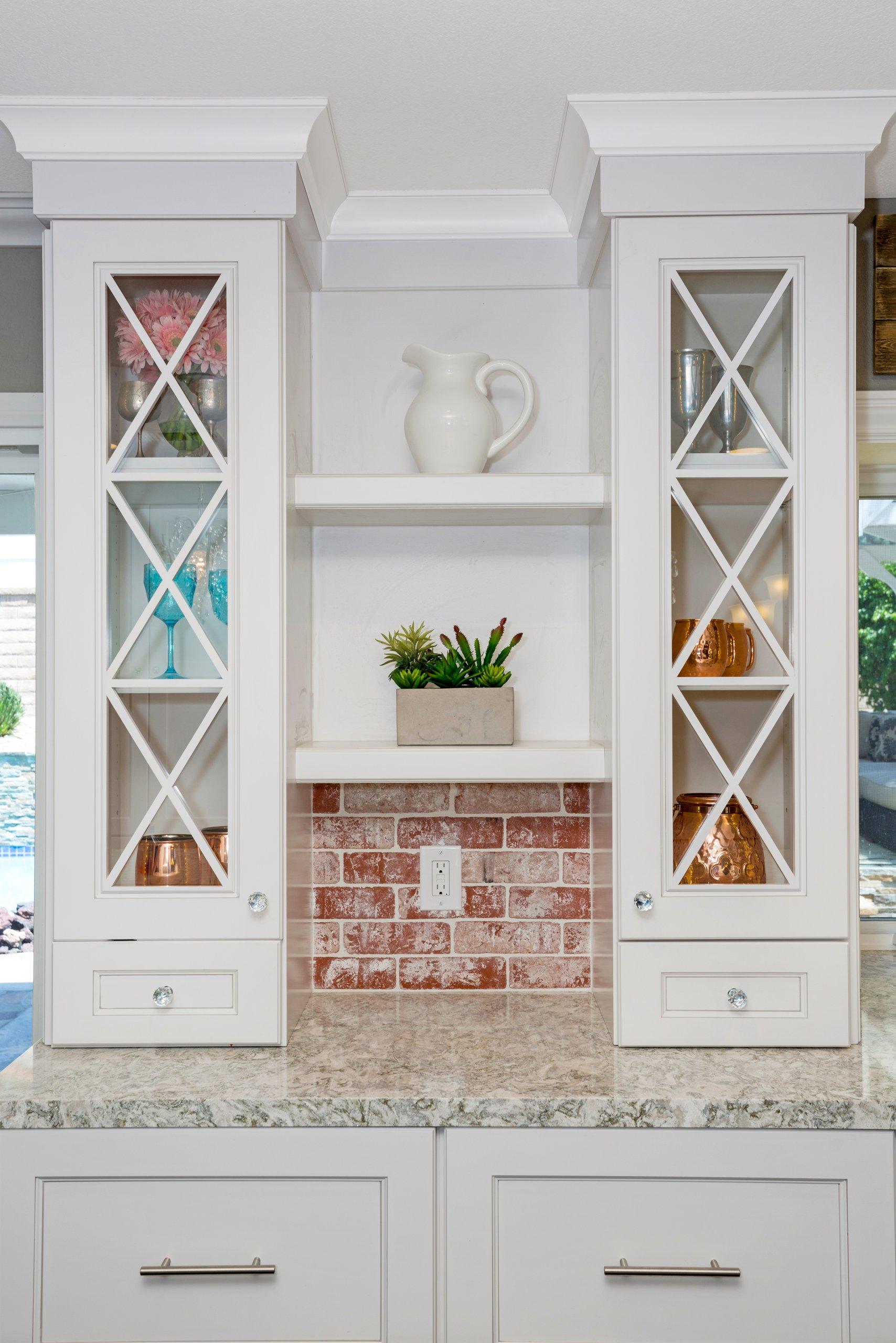 Tall white butler's pantry with brick backsplash.