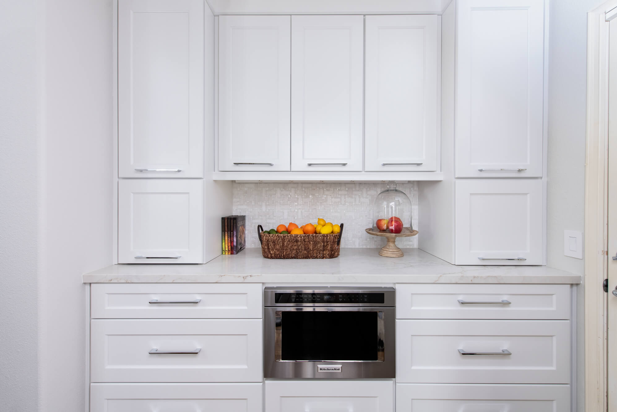 butlers-pantry-with-cabinetry-and-marble-tile