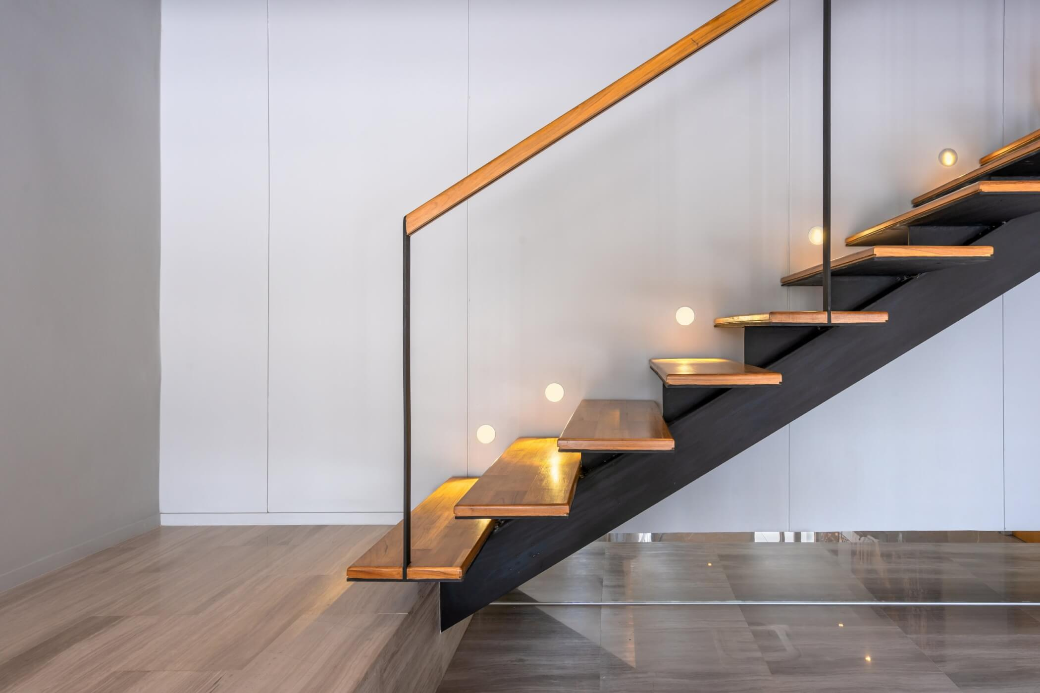 a modern staircase with lights and a glass baluster