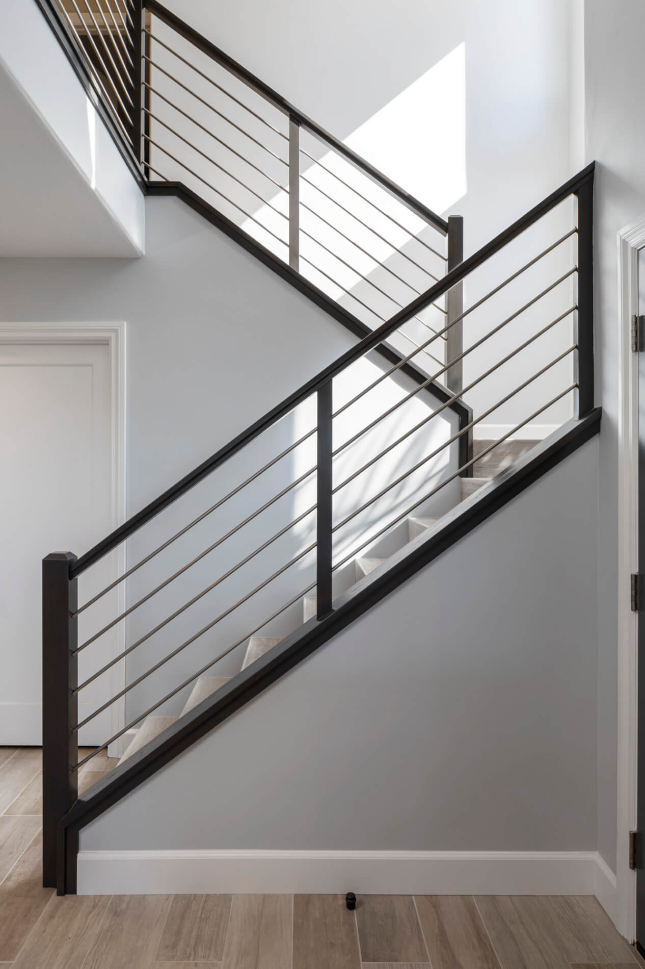 a white staircase with black railing