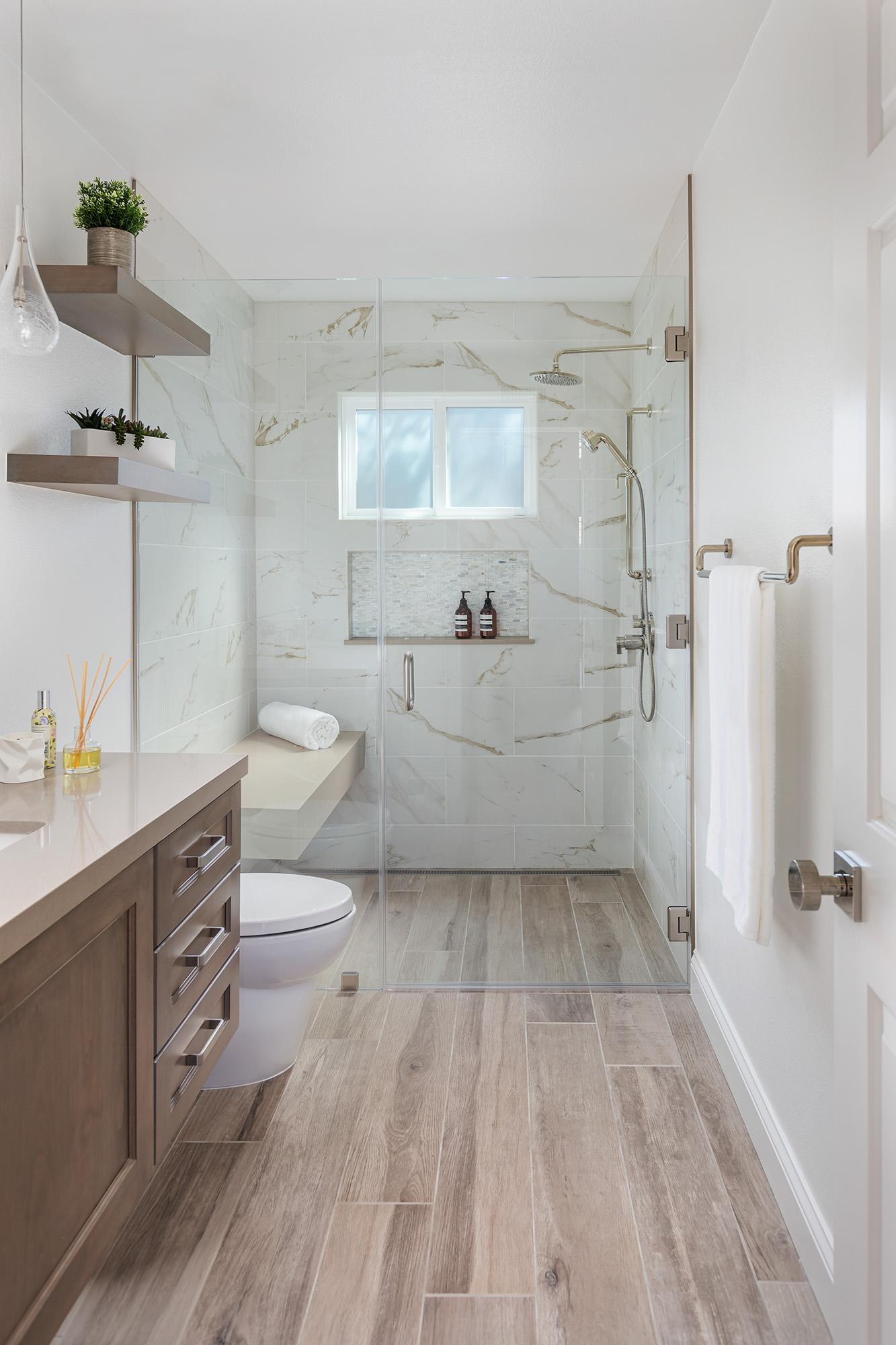 Bathroom with white tub, glass shower, black and white tiled floor