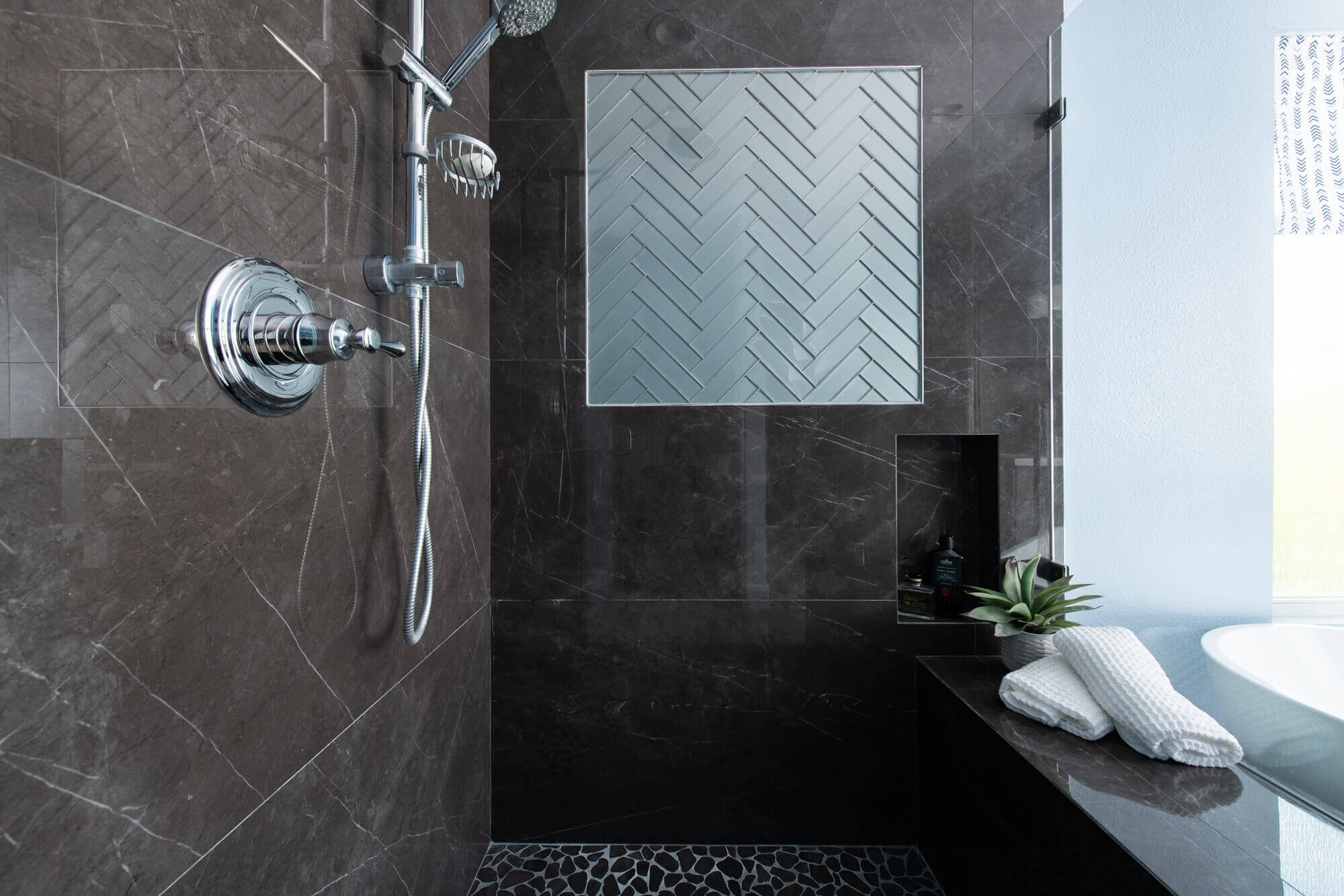 Shower with large dark tiles