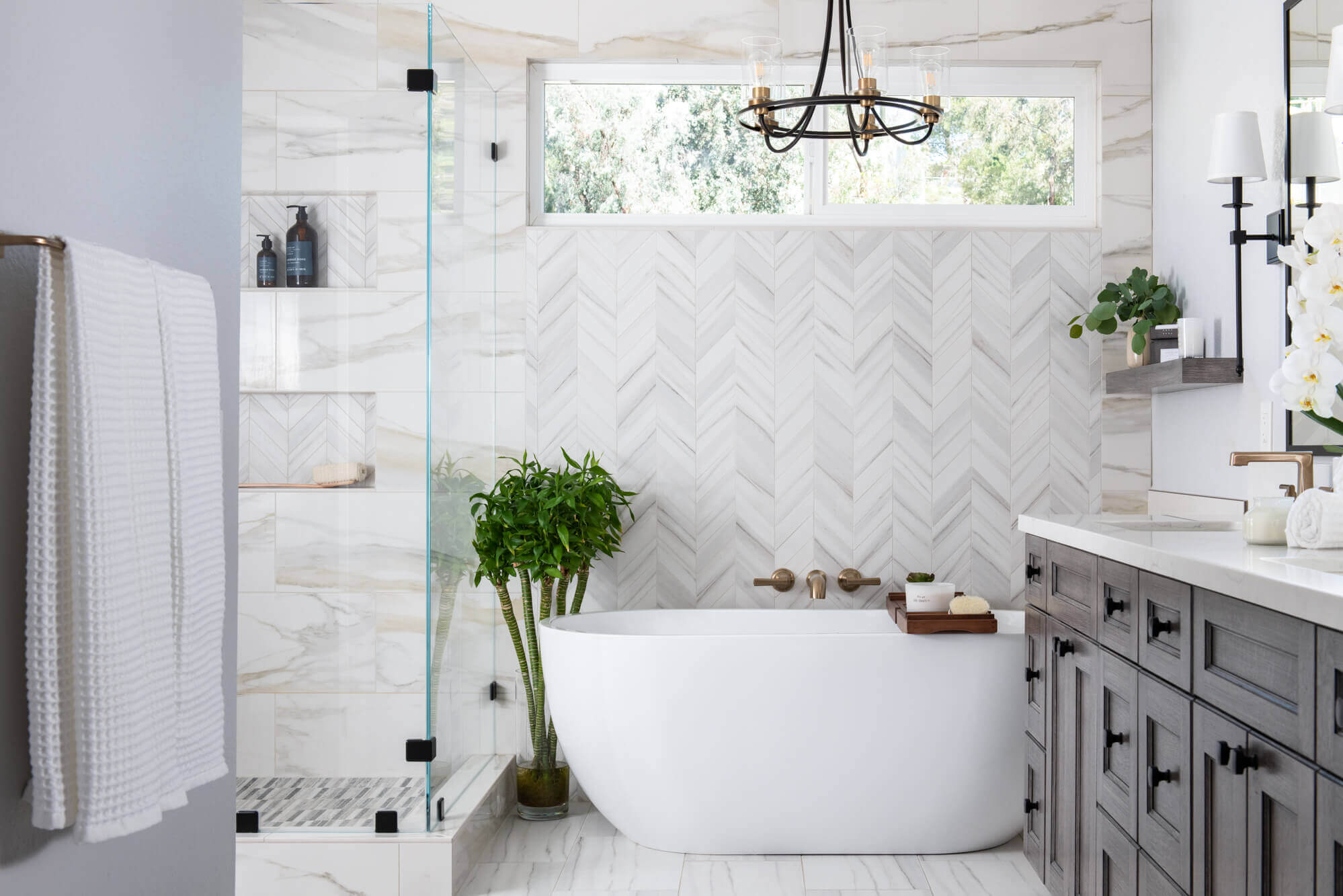athroom with white tub, glass shower, black and white tiled floor