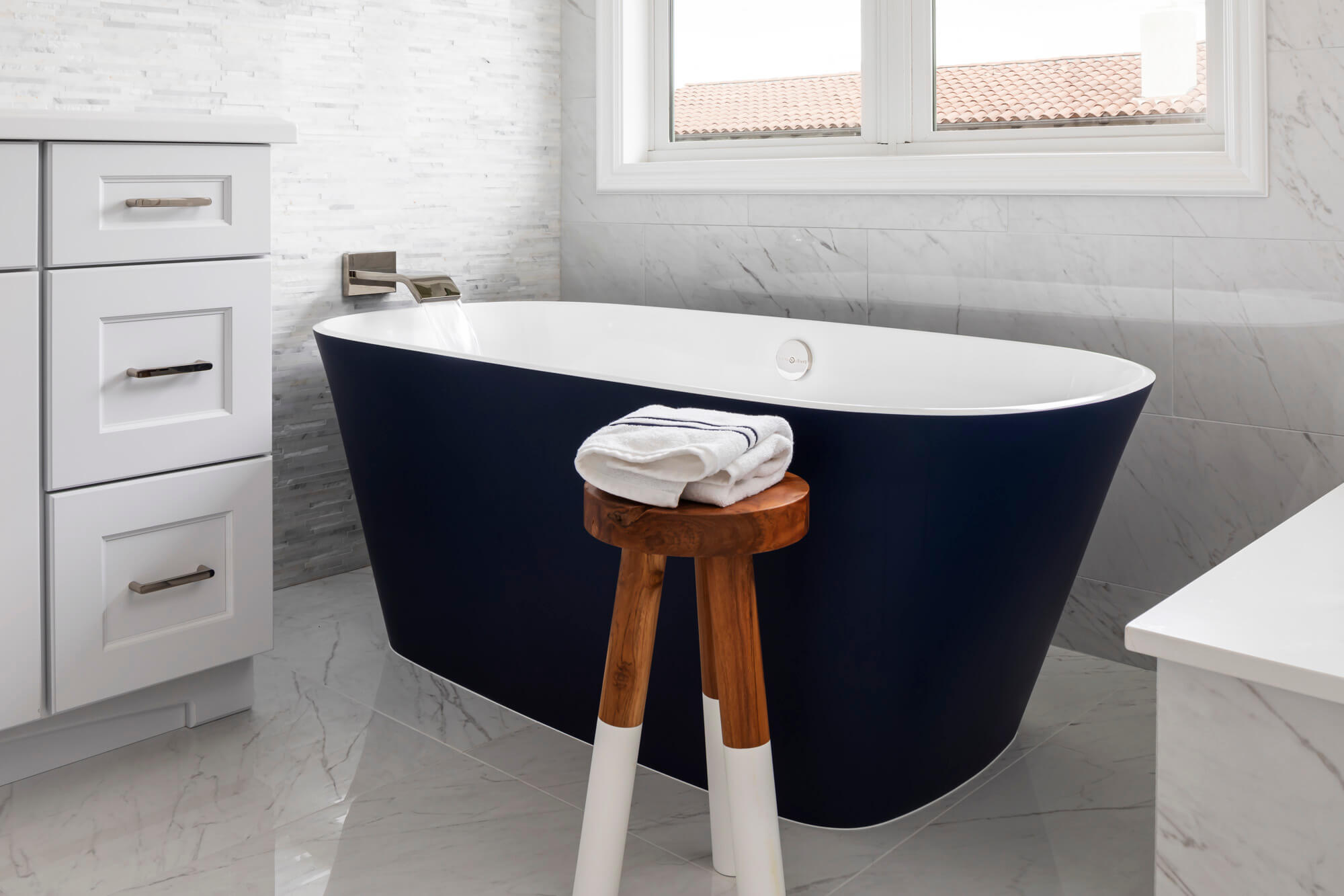 : Black bathtub in white bathroom