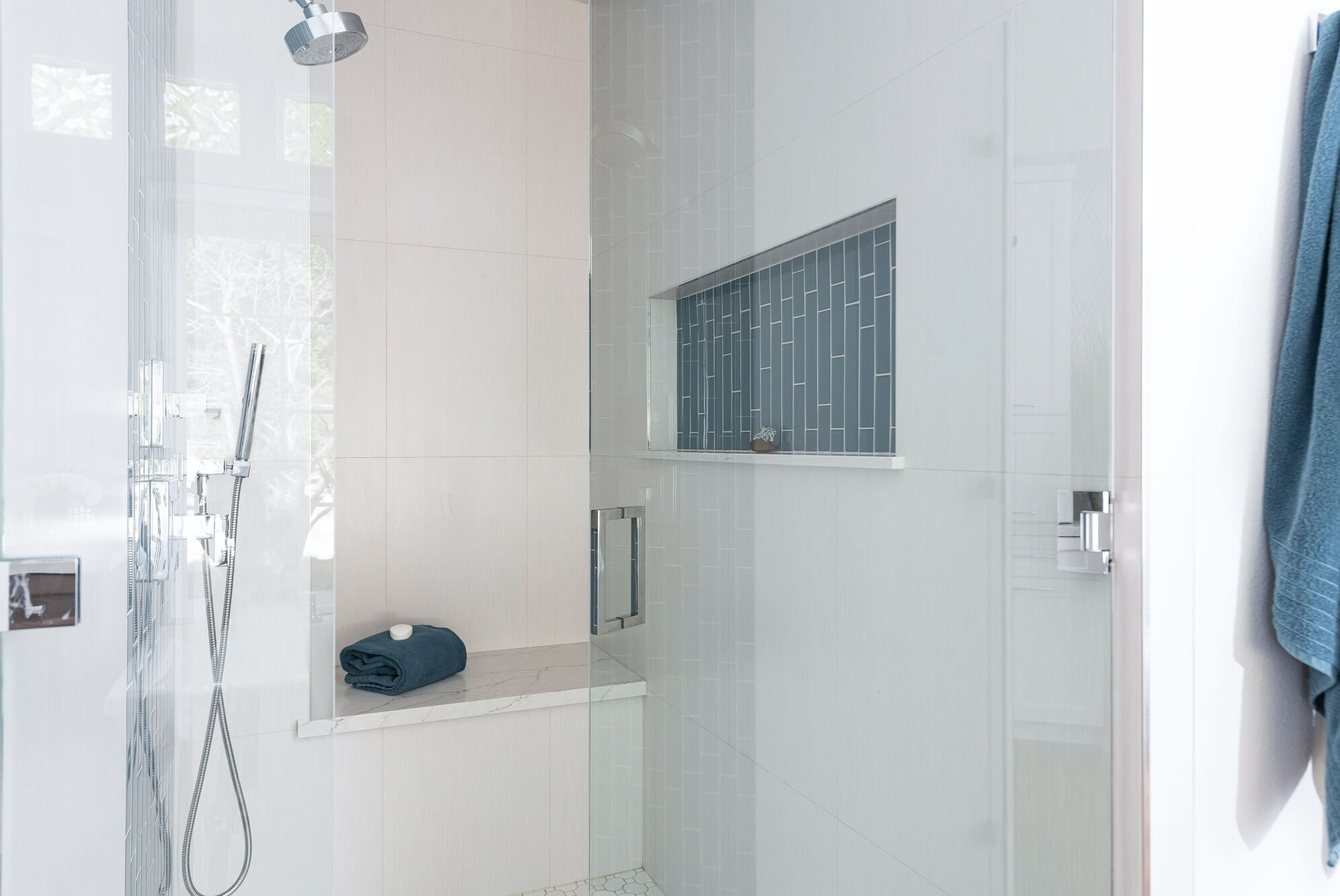 Glass shower with white tiles